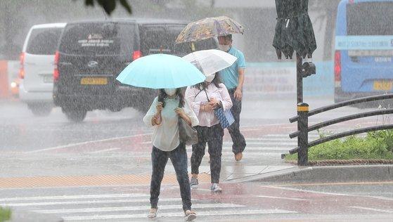 전국 곳곳에 호우특보가 내려진 29일 오전 서울 종각역 인근에서 우산 쓴 시민들이 발걸음을 재촉하고 있다. 뉴스1
