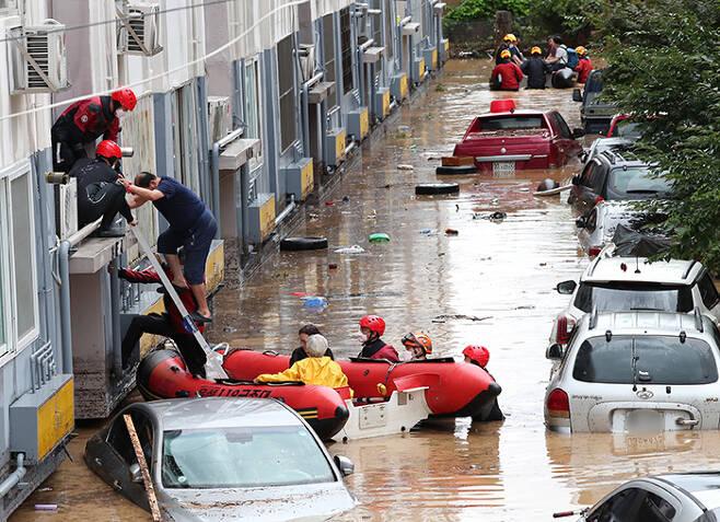 30일 대전 서구의 한 아파트에서 집 안에서 구조를 기다리던 주민들이 119구조대의 도움을 받아 고무보트에 타고 있다. 빗물은 구조대원들의 허리 높이까지 차올랐고 아파트에 주차된 차들은 침수됐다. /신현종 기자