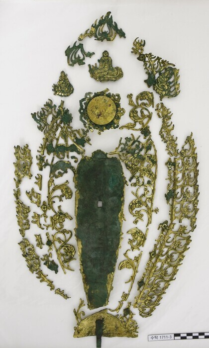 금동보살상 뒤에 따로 제작해 붙였던 광배를 따로 수습한 모습. 불꽃무늬와 넝쿨무늬, 가부좌한 불상 무늬 등이 보인다.