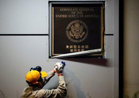 26일(현지시간) 한 남성이 중국 청두 주재 미 영사관에 붙어 있는 미국 현판을 제거하고 있다. [로이터=연합뉴스]