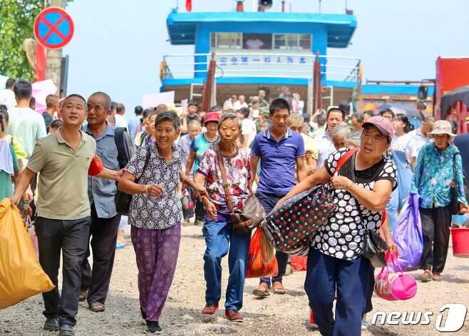 14일 (현지시간) 중국 최대 담수호인 장시성 주장의 포양호가 계속된 폭우로 범람 위기에 처하자 주민들이 대피를 하고 있다. © AFP=뉴스1 © News1 우동명 기자