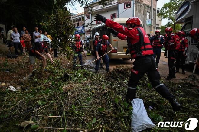 16일 (현지시간) 중국 최대 담수호인 포양호 인근 장시성 상라오의 폭우로 물에 잠긴 마을을 구조대원들이 정리를 하고 있다. © AFP=뉴스1 © News1 우동명 기자