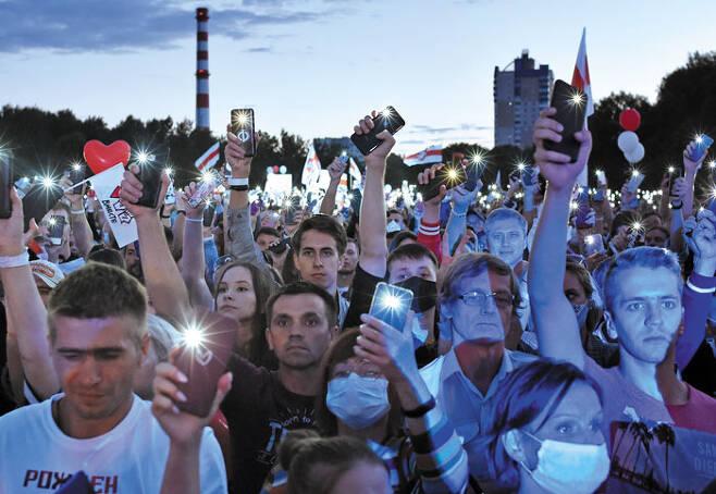 30일(현지 시각) 벨라루스 수도 민스크에 모인 시민들이 휴대전화 불빛을 밝히며 알렉산드르 루카셴코 벨라루스 대통령을 비판하는 시위를 하고 있다. 이들은 오는 8월 9일 대선을 앞두고 선거관리위원회가 주요 야권 정치인에 대해 대선 후보 등록을 거부하고 있는 것을 규탄했다. /AFP 연합뉴스