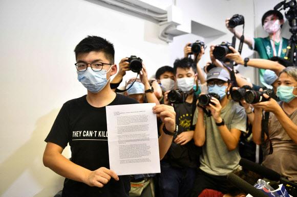 선거 출마 봉쇄 당한 홍콩 우산 혁명 주역 조슈야 웡 - 홍콩 우산 혁명이 주역인 조슈아 웡이 31일 기자회견에서 오는 9월의 입법회(의회) 선거에 출마할 자격이 없다는 선거관리위원회의 통보서를 들어보이고 있다. 조슈아 웡은 이날 회견에서 홍콩 민주 진영이 중국의 정치적 탄압에 계속 저항할 것이라고 다짐했다. 2020.7.31 AFP 연합뉴스