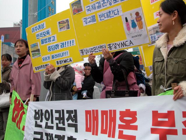 지난 2006년 동남아에서 충남 홍성으로 시집와 생활하고 있는 이주여성들이 자신들을 상품으로 전락시키고 매매혼을 부추기는 국제결혼 알선업체의 플래카드를 철거할 것을 촉구하고 있다./연합뉴스