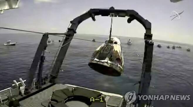 해상에서 선박으로 인양되는 스페이스X 캡슐 (멕시코만 로이터=연합뉴스) 미국 항공우주국(NASA) 우주비행사 봅 벤켄과 더그 헐리가 탑승한 스페이스X 캡슐이 2일(현지시간) 멕시코만 해상에서 선박 위로 인양되고 있다. NASA 영상을 캡처한 사진. [NASA 제공] sungok@yna.co.kr