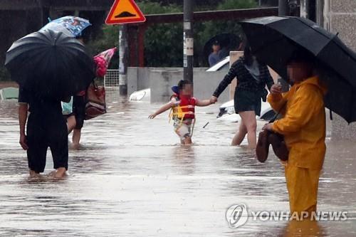 구명조끼 입고 피신 (광주=연합뉴스) 정회성 기자 = 8일 오전 폭우로 침수된 광주 광산구 선운동 주택가에서 구명조끼를 입은 어린이가 가족과 함께 피신하고 있다.