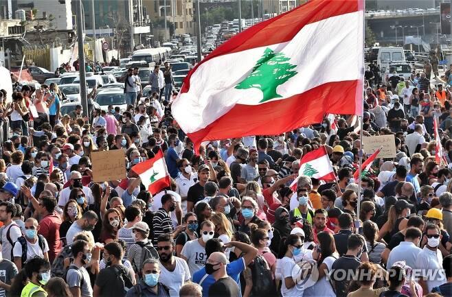 (베이루트 EPA=연합뉴스) 레바논 대규모 폭발참사 일주일을 맞은 11일(현지시간) 반정부 시위대가 폭발 현장인 베이루트 항구 근처에 모여 희생자들을 추모하고 있다. leekm@yna.co.kr