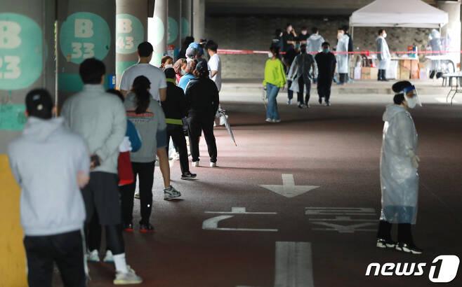 쿠팡 물류센터 근로자들이 지난 5월26일 부천 종합운동장에 마련된 선별진료소에서 검사를 받기 위해 줄을 섰다./뉴스1 © News1 정진욱 기자
