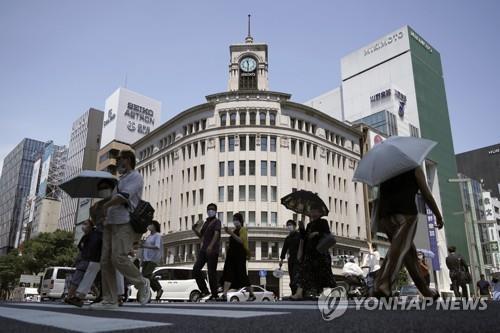 (도쿄 AP=연합뉴스) 12일 일본 도쿄도(東京都) 중심가에서 양산을 쓴 사람들이 이동하고 있다.