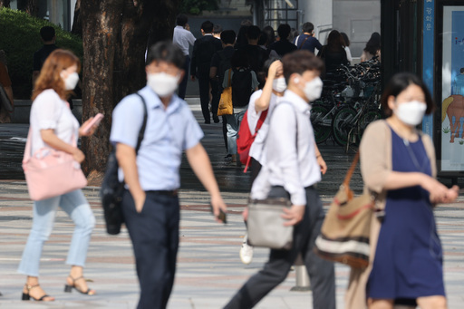 19일 오전 서울 종로구 광화문네거리에서 마스크를 쓴 시민들이 발걸음을 재촉하고 있다. 연합뉴스