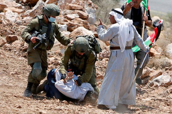이스라엘 군인들이 20일(현지시간) 팔레스타인 요르단강 서안지구의 툴카름 유대인 정착촌 앞에서 팔레스타인 시위대를 체포하고 있다. 툴카름   로이터연합뉴스