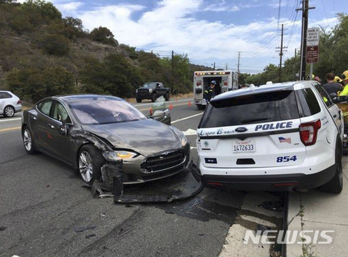 【라구나비치=AP/뉴시스】미국 캘리포니아주 라구나비치에서 29일(현지시간) 테슬라 자동차(왼쪽)가 자율주행 중 경찰SUV를 들이 받은 후 멈춰 서있다. 2018.05.30