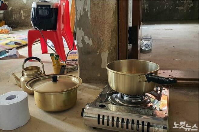 남원 하도마을에 사는 조봉금(70)씨는 장판이 뜯겨진 집 거실에서 휴대용 버너로 음식을 만들고 있다. (사진= 남승현 기자)