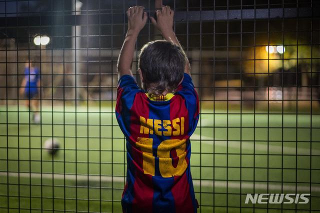 [바뇰레스=AP/뉴시스]2일(현지시간) 스페인 헤로나주 바뇰레스에서 리오넬 메시의 이름과 등 번호가 새겨진 셔츠를 입은 한 소년이 지역 축구 경기를 보고 있다. 한 소식통은 이날 메시의 부친과 바르셀로나 구단 관계자와의 첫 면담이 아무런 합의 없이 끝났다고 AP 통신을 통해 전했다. 메시는 2021년 여름까지 바르셀로나와 계약이 돼 있으나 일방적으로 이를 해지할 수 있다. 2020.09.03.