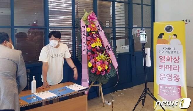 제주 한 결혼식장에서 하객들을 상대로 명부 작성과 발열검사를 하고 있다(서귀포시 제공) /© 뉴스1