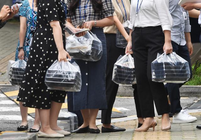 지난달 31일 사회적 거리두기 2.5단계가 시작되며 서울시 중구에서 직장인들이 점심 시간에 맞춰 주문한 도시락을 들고 빌딩 안 사무실로 향하고 있다. 고영권 기자