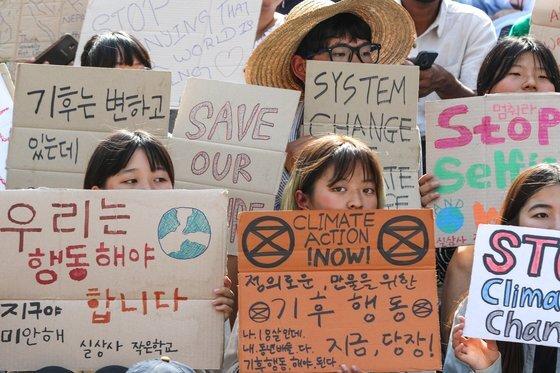 """지난해 5월 서울 종로구 세종문화회관 앞에서 한국청소년기후소송단 회원들이 '524 청소년 기후행동 기후변화 대응 촉구 집회'를 진행하는 모습입니다. 청년 기후변화 활동가들은 """"최근 몇 년 새 규모가 작은 청년 기후변화 단체들이 조금씩 늘고 있다""""고 전했죠. 뉴스1"""