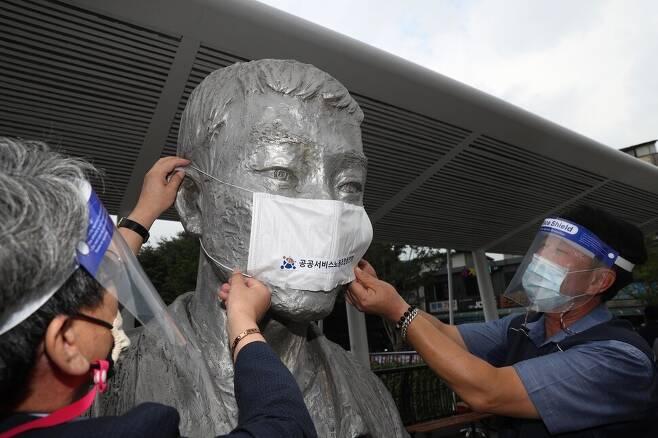 16일 오전 서울 종로구 전태일다리에서 열린 '제16차 전태일 50주기 캠페인'에서 참석자들이 전태일 동상에 마스크를 씌우고 있다. 김봉규 선임기자