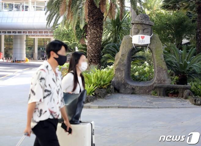 30일 오전 제주국제공항에 마스크를 쓴 관광객들이 이동하고 있다. 전날 제주에는 신종 코로나바이러스 감염증(코로나19) 확진자 4명이 추가 발생했다. 2020.8.30/뉴스1 © News1 홍수영 기자