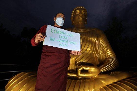 """최근 인도에서는 힌두교 대신 불교로 개종하는 이들이 늘고 있다. 카스트 제도로 자식까지 계급을 이어받는 것에 불만을 품으면서다. 사진은 올해 인도 불교 사원에서 """"코로나는 지고 세계는 승리할 것""""이라는 문구가 적힌 종이를 든 남성. [EPA=연합뉴스]"""