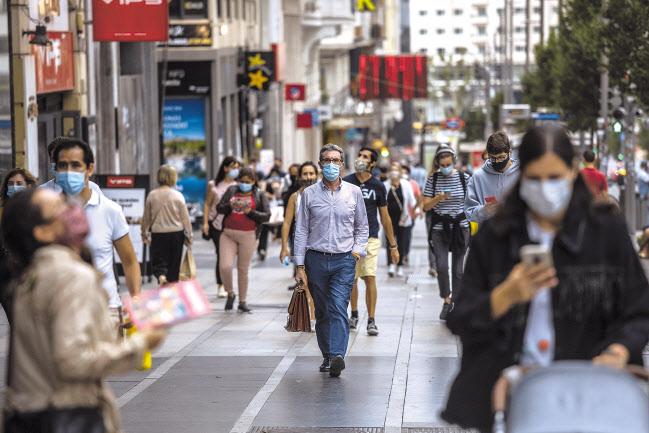 17일(현지시간) 스페인 수도 마드리드 시민들이 모두 마스크를 착용한 채 거리를 걷고 있다. 국제통계사이트 월드오미터에 따르면 이날 스페인의 코로나19 신규 확진자 수는 1만1291명을 기록하며 전날(1만1193명)에 이어 이틀 연속 1만명 선을 돌파했다. [AP]