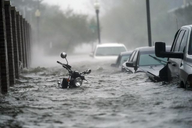 지난 16일(현지시간) 허리케인 샐리의 영향으로 집중호우가 발생하자 미국 플로리다주 팬서콜라 지역에 차와 오토바이가 거의 물에 잠겨있다./AP연합뉴스