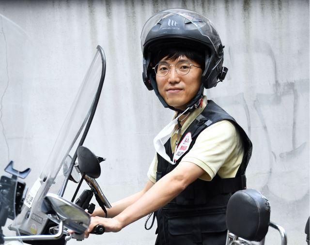 """박정훈 라이더유니온 위원장이 지난 18일 서울 마포구 사무실 앞에서 배달할 때 입는 헬멧과 조끼를 착용하고 포즈를 취했다. 그는 봄·가을은 라이더들에게는 비수기이지만 다가오는 추석 연휴가 한가하지 않을 거라고 했다. """"저도 배달할 생각입니다. 서울은 1인 가구가 많고 고향에 내려가기 싫어하는 젊은 친구들 수요가 있잖아요. 제사 음식이 물릴 때쯤 배달음식을 찾는 경우도 많고요."""" 최종학 선임기자"""