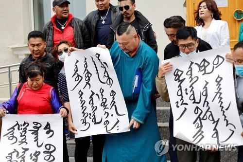 지난달 31일 몽골 울란바토르 외교부 밖에서 몽골어로 쓴 플래카드를 든 시위 참가자들이 중국에 항의하고 있다. [로이터=연합뉴스 자료사진]