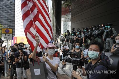 지난7월4일 미국 독립기념일에 홍콩주재 미국총영사관 부근에서 성조기를 흔들다 저지되는 여성. [AP=연합뉴스]