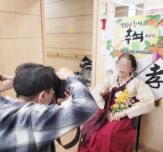 서울 강동우리들병원 사회복지사가 한복을 곱게 차려입은 할머니 모습을 촬영하고 있다. 사진 강동우리들병원