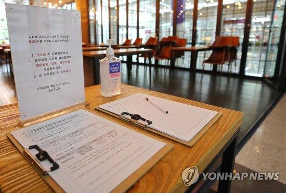 서울 강남구의 한 카페 입구에 이용 고객이 작성해야 하는 수기 출입 명부가 놓여 있다. 연합뉴스
