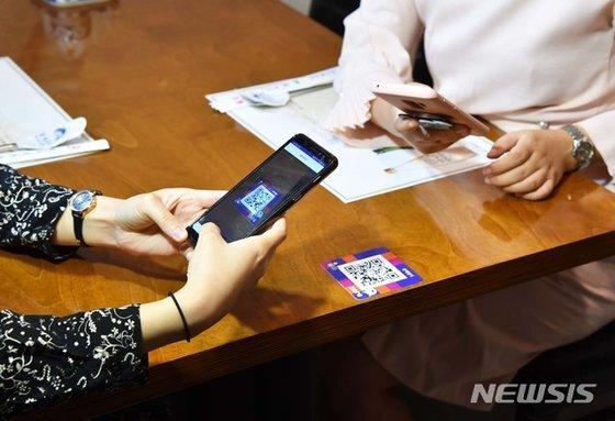 서울시 관계자들이 지난달 18일 서울 중구에 위치한 한 음식점에서 제로페이 QR 코드를 활용한 전자출입명부 관리 시연을 하고 있다. 뉴시스