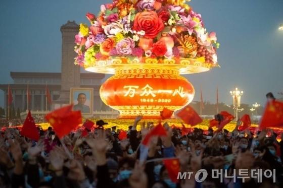 [베이징=신화/뉴시스] 중국 베이징 톈안먼 광장에서 1일 공산중국 수립을 축하하는 국경절을 맞아 열린 오성홍기 게양식을 지켜보기 위해 몰린 군중이 기념 조형물에 불이 들어오자 작은 깃발을 흔들며 환호하고 있다. 2020.10.01