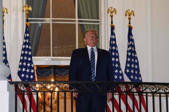 도널드 트럼프 미국 대통령이 5일 월터리드 군병원에서 퇴원해 백악관에 복귀한 뒤 마스크를 벗고 카메라를 응시하고 있다. [AFP=연합뉴스]