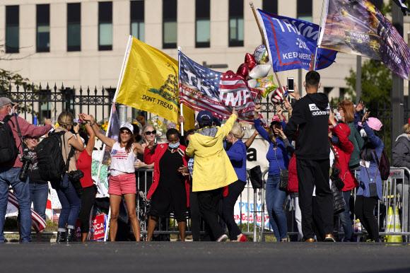도널드 트럼프 미국 대통령이 5일 오후(이하 현지시간) 퇴원하겠다고 예고한 가운데 메릴랜드주 베데스다의 월터 리드 군 병원 앞을 지키는 지지자들이 조속한 백악관 복귀를 바라며 환호하고 있다.베데스다 AP 연합뉴스