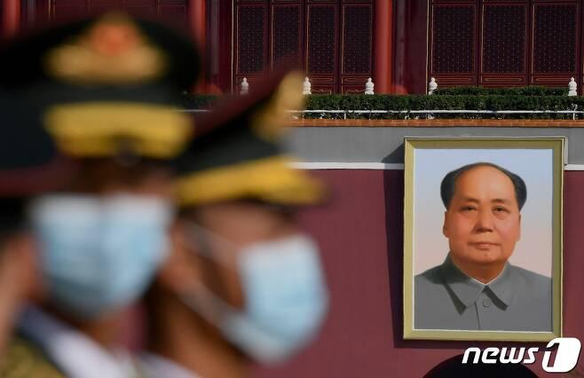 지난달 30일 중국 '국가열사기념일'을 맞아 베이징 톈안먼 광장에서 열린 기념식에 참석한 중국군 의장대(왼쪽) 뒤로 마오쩌둥 전 국가주석의 초상화가 보인다. © AFP=뉴스1