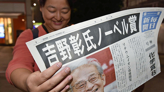 지난해 10월 일본 도쿄 시내 거리에서 행인이 요시노 아키라가 노벨 화학상 수상자로 결정됐다는 호외 신문을 읽고 있다. [사진 출처 : 교도=연합]