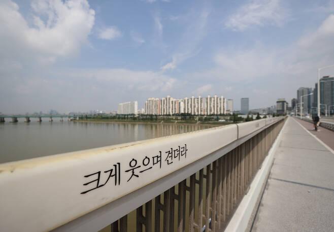세계 자살예방의 날인 10일 서울 한강 한강대교 보도 난간에 '크게 웃으며 견뎌라'는 문구가 새겨져 있다. [연합]