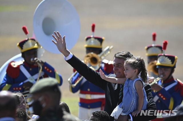 [브라질리아=AP/뉴시스]자이르 보우소나루 브라질 대통령이 7일(현지시간) 수도 브라질리아에서 열린 독립기념 행사에 참석해 한 아이를 안고 지지자들에게 인사하고 있다. 브라질은 1822년 9월 7일 포르투갈로부터 독립을 선언했다. 2020.09.07.