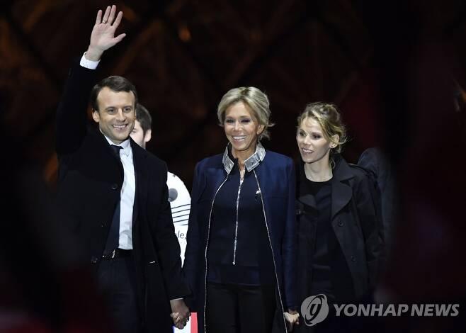 2017년 5월 7일 프랑스 대선 승리 직후 에마뉘엘 마크롱(왼쪽)이 손을 치켜든 채, 부인 브리지트 마크롱(가운데), 의붓딸 티판 오지에르(오른쪽)와 함께 기뻐하고 있다. [EPA=연합뉴스 자료사진]