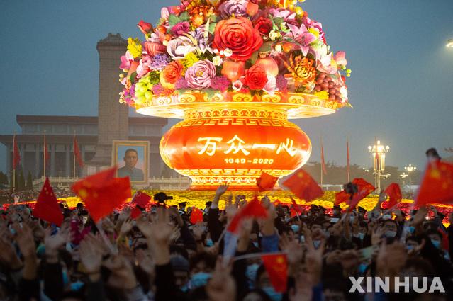 [베이징=신화/뉴시스] 중국 베이징 톈안먼 광장에서 지난 1일 공산 중국 수립을 축하하는 국경절을 맞아 열린 오성홍기 게양식을 지켜보기 위해 몰린 군중이 기념 조형물에 불이 들어오자 작은 깃발을 흔들며 환호하고 있다. 2020.10.09