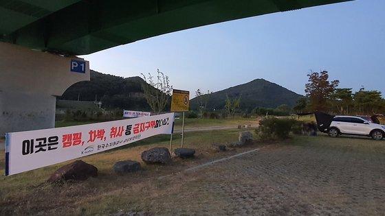 지난 9일 오후 충남 공주시 공주보 공도교 아래 주차장에 캠핑과 차박, 취사를 금지한다는 플래카드가 설치돼 있다. 하지만 이곳에는 캠핑카가 밤샘 주차했고 일부 나들이객은 텐트도 설치했다. 신진호 기자