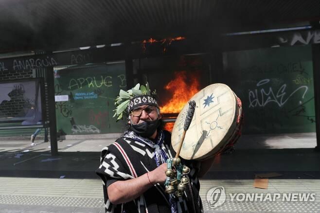 12일(현지시간) 칠레 산티아고에서 현지 원주민인 마푸체족을 옹호하는 수백명이 반정부 시위를 벌였다. 일부 시위대는 버스 정류장 등을 파손하고 경찰과 충돌했다. [로이터=연합뉴스]