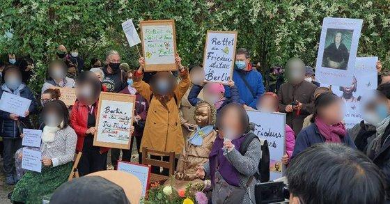 13일 독일 수도 베를린에서 시민들이 거리에 설치된 '평화의 소녀상'에 대한 당국의 철거명령에 항의하기 위해 미테구청 앞에서 집회를 하고 있다. [사진제공=현지교민]