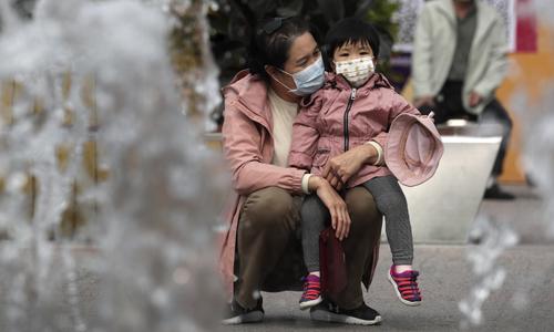11일 베이징의 한 쇼핑몰에서 마스크를 쓴 여성과 아이가 분수대를 지켜보고 있다. 베이징=AP연합뉴스