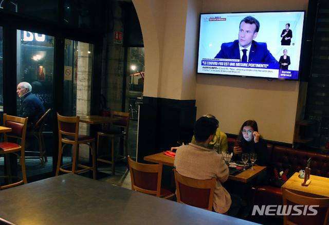 [생장드뤼즈=AP/뉴시스] 14일(현지시간) 프랑스 남서부 생장드뤼즈의 한 식당에서 에마뉘엘 마크롱 프랑스 대통령의 대국민담화가 방송되고 있다. 마크롱 대통령은 17일부터 코로나19 방역을 강화하기 위한 국가 보건 비상사태를 시행한다고 밝혔다. 또 코로나19의 확산이 심각한 지역에서는 야간 통행금지 조치를 실시한다. 2020.10.15.