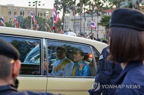 수티다 왕비와 디빵꼰 왕세자가 탄 차량을 향해 반정부 시위대가 세손가락 경례를 하는 모습이 뒤로 보인다. 2020.10.14  [AFP=연합뉴스] [2020.10.15 송고]