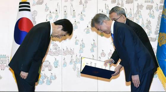 문재인 대통령(오른쪽)이 9일 오전 청와대에서 열린 임명장 수여식에서 이주열 한국은행 총재에게 임명장을 수여하고 있다. [청와대사진기자단]