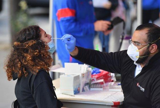 미국 뉴욕시의 코로나19 감염률이 급증한 가운데 지난 8일 브루클린 지역에서 의료진이 코로나19 검사를 위해 코 면봉 샘플을 채취하고 있다. AFP=연합뉴스
